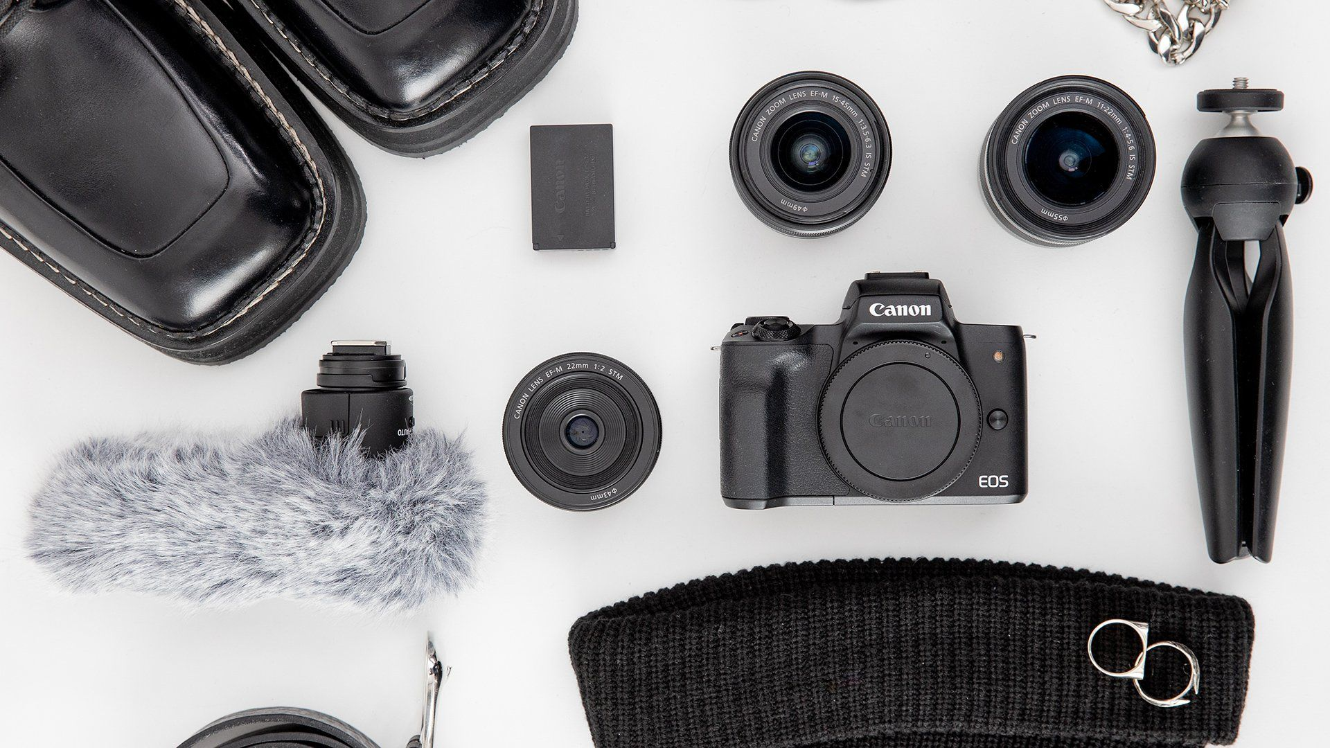 A flatlay of a vlogger's equipment, including the Canon M50.